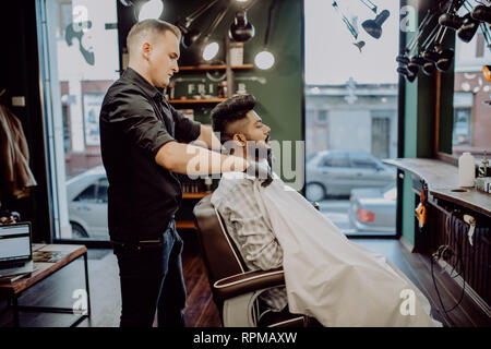 Handsome bearded man is smiling while having his hair cut by hairdresser at the barbershop - Stock Photo