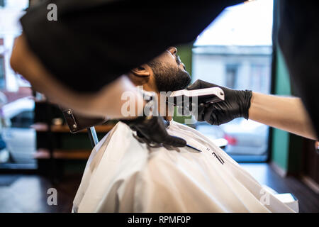 Grooming of real man. Side view of young bearded man getting beard haircut at hairdresser while sitting in chair at barbershop Stock Photo