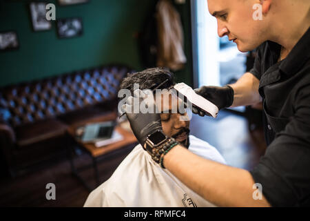 Unshaven man being clipped with professional electric shearer machine in barbershop. Male beauty treatment concept. Indian guy trim beard and mustache - Stock Photo