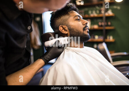 Young bearded man getting haircut by hairdresser with electric razor while sitting in chair at barbershop - Stock Photo