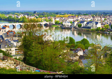 Breathtaking view on amazing small town Saumur, France. Many white and gray houses near a Loire river, arched bridge, lots of green trees and rooftops - Stock Photo