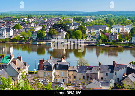 Breathtaking view on amazing small town Saumur, France. Many white and gray houses near a Loire river, lots of green trees and rooftops. Warm spring m - Stock Photo