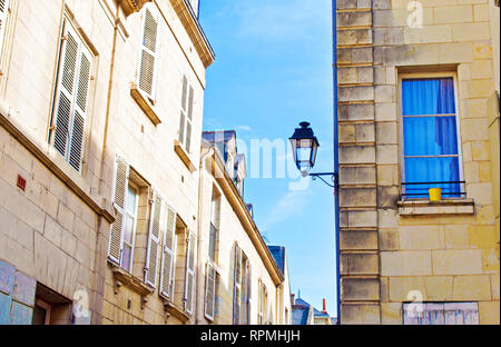 Grande Rue street in the city center of a small town Saumur, France. Many white houses with shutters, one lantern and yellow flower pot. Warm spring m