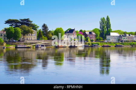 Breathtaking view on amazing small town Saumur, France. Many gray houses near Loire river, lots of green trees, a row of colorful boats. Warm spring m - Stock Photo