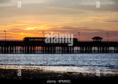 1930s tube train on Ryde Pier in silhouette against sunset, Island Line, railway, Sandown, Shanklin, UK, England, Isle of Wight, Ryde - Stock Photo