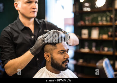 Bearded man with long beard, brutal, indian hipster with moustache, with stylish hair, haircut, getting powder on skin with make up brush by barber or - Stock Photo