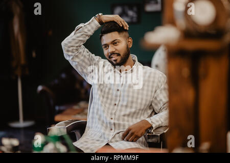 Time for new haircut. Handsome bearded man looking at his reflection in the mirror and keeping hand in hair while sitting in chair at barbershop - Stock Photo