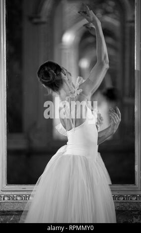 Beautiful ballerina dancing in front of the mirror. Black and white image. - Stock Photo