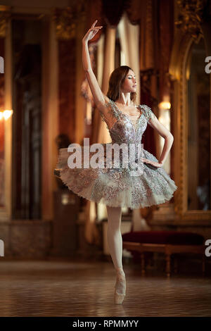 Beautiful ballerina dancing in a hall against the luxurious interior. Arabesque ballet pose. - Stock Photo
