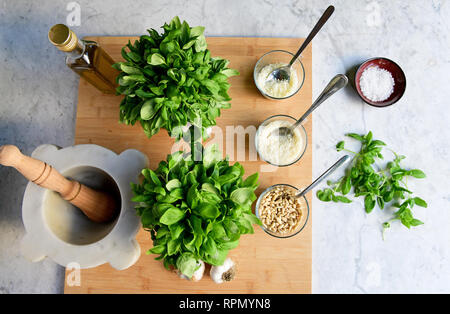 All the ingredients for a proper pesto are laid out on a marble table - Stock Photo