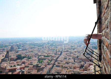 Detail of a man's arm leaning out one of the windows on top of the  Asinelli tower in Bologna, Italy - Stock Photo