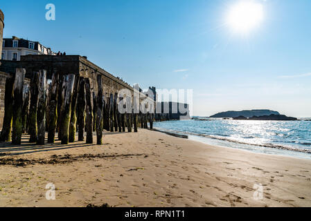 Saint-Malo, France - July 24, 2018: Wooden poles and Saint Malo walls at high tide. Brittany, France, Europe - Stock Photo