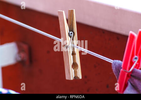 Set of three wooden cloth pegs on rope . - Stock Photo