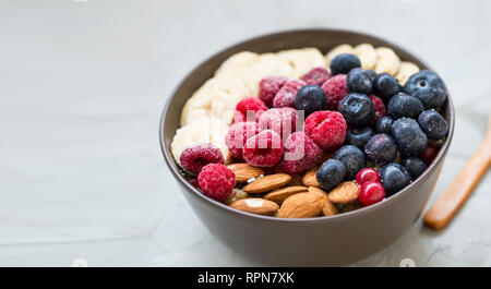 Healthy breakfast with acai bowl, raspberries, blueberries, almonds, bananans , healthy granola or muesli bowl with fresh berries, fresh ingredients - Stock Photo