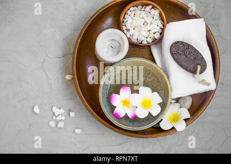 Spa products in wooden tray, top view of spa items with frangipani flowers, candle, bath salt, towel and ponce stone, spa still life setting - Stock Photo