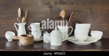 Crockery, porcelain, white utensils and other different stuff on wooden countertop. Kitchen still life as background for design. - Stock Photo