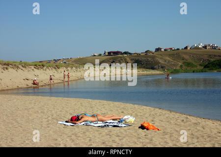 Black Sea, Sinemorets, Bulgaria. The  estuary of the Veleka River. 10 August 2005. A young woman lying on beach at swimsuit. In the distance tourists  - Stock Photo