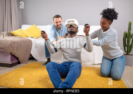 Amazed shoked surprised african man wearing virtual reality glasses while two diverse multiracial friends sitting on couch and smiling - Stock Photo