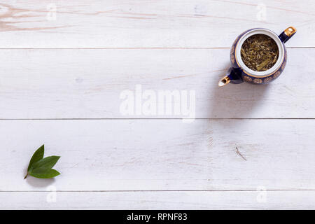 Teapot and tea time leaves set on white wooden table, black herbal homemade hot beverage in porcelain pot with green leaf, english tea ceremony backgr - Stock Photo