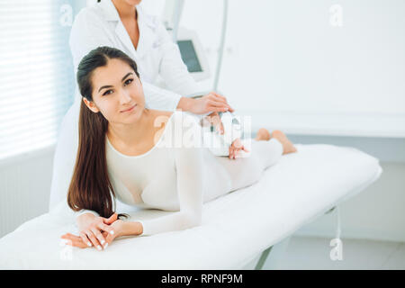 Portrait of brunette woman dressed in white LPG slimming bodysuit, looking at camera while getting lpg integral massage, which is carried out by the l - Stock Photo