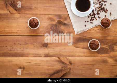 Cup of black coffee, muffins and coffe beans scattered on brown wooden table, cofee cafe cafeteria shop background, hot drink in mug with cakes mornin - Stock Photo