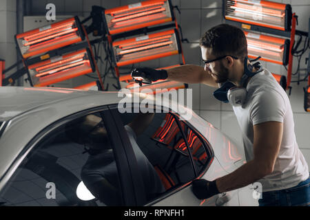 guy using a car paint thickness checker at workplace at the garage. close up photo - Stock Photo