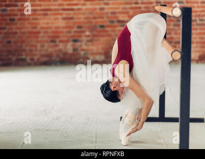 ballerina doing exercises in the loft room, full length side view photo. copy space - Stock Photo