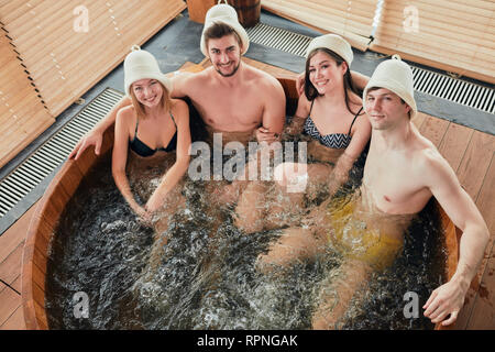 Two relaxing caucasian couples spend their day off in luxury spa centre, sharing ideas and news while taking a whirlpool bubble bath. Sauna, therapy,  - Stock Photo