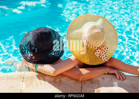 Mother and her adult daughter relaxing in hotel swimming pool. People enjoying summer vacation. Mother's day - Stock Photo