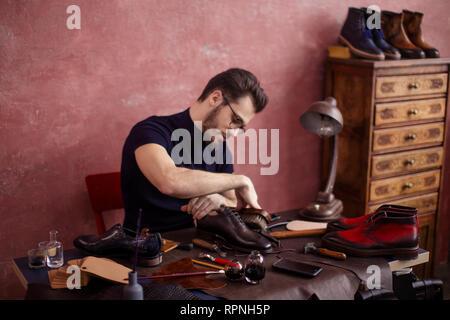 A shoeshine man polishing a leather dress shoe - Stock Photo