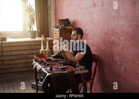 shoe designer working with a brush while sitting at the table . side view photo - Stock Photo