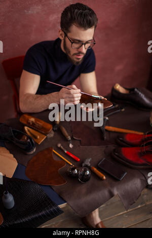 young designer using a brush while working in the shoe shop with moderrn interior. close up photo - Stock Photo