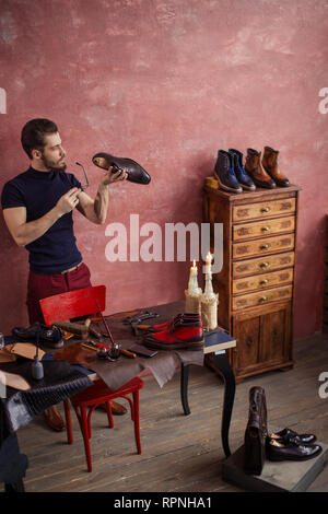 clever shoemaker examining the damaged heel ogf footwear, full length photo. copy space - Stock Photo