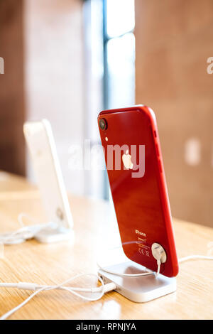 PARIS, FRANCE - OCT 26, 2018: Side view of glossy red latest iPhone XR smartphone in Apple Store Computers during the launch day - shiny silver logotype - Stock Photo