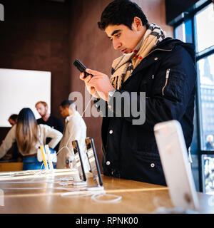 PARIS, FRANCE - OCT 26, 2018: Side view of young male customer admiring the latest iPhone XR smartphone in Apple Store Computers during the launch day - square image - Stock Photo