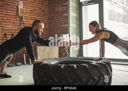 Caucasian crossfit male coach shows crossfit plyometric push-up technique, performed on truck tire to his female trainee , encouraging her with hand.