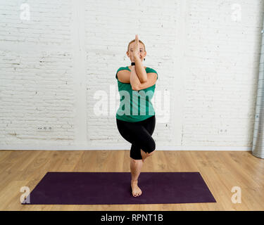 Portrait of attractive yogi woman teacher practicing advanced yoga in Eagle Pose Garudasana at cool urban studio in Fitness Yoga benefits and Emotiona - Stock Photo