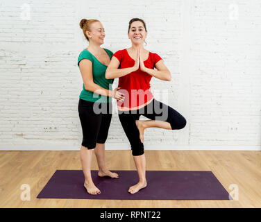 Portrait of Yoga couch instructor helping young woman friend practicing together yoga standing in Tree pose workout exercise in urban style studio in  - Stock Photo