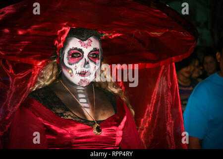 A blond girl wearing traditional skull make up and red dress and big hat, is celebrating the famous Dia de los muertos in Merida, Yucatan, Mexico - 31 - Stock Photo