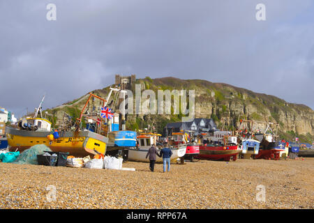 Couple strolling past Hastings fishing boats on the Old Town Stade beach on a stormy day in winter, East Sussex, UK - Stock Photo