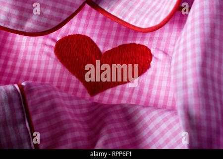 Pink and white checked gingham fabric with red heart. Cotton nightwear. - Stock Photo