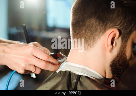 Master cuts hair and beard of men in the barbershop - Stock Photo