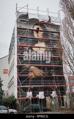 Berlin, Germany. 21st Feb, 2019. With the help of a scaffold, three sprayers complete the huge Mona Lisa mural on the house of the East Side Hotel. Credit: Annette Riedl/dpa/Alamy Live News - Stock Photo