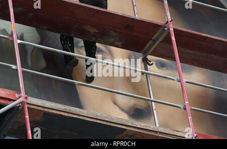 Berlin, Germany. 21st Feb, 2019. A sprayer, sitting on the scaffold, completes the huge mural of the Mona Lisa at the house of the East Side Hotel. Credit: Annette Riedl/dpa/Alamy Live News - Stock Photo