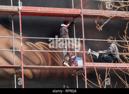 Berlin, Germany. 21st Feb, 2019. Two sprayers on the scaffold complete the huge mural on the house of the East Side Hotel. These are the hands of Mona Lisa. Credit: Annette Riedl/dpa/Alamy Live News - Stock Photo