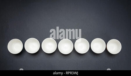 White clean ceramic bowls in a row, black color background, copy space, top view - Stock Photo