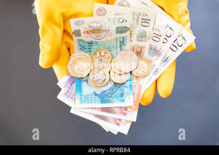 A pair of hands wearing yellow rubber gloves holding pound notes & coins. Concept cash in hand, black economy or low pay. - Stock Photo