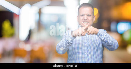 Middle age arab business man over isolated background Rejection expression crossing fingers doing negative sign - Stock Photo