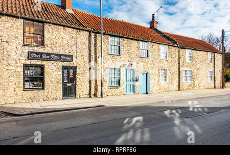 English Village Neat row of stones cottages and shop in Market Place, Tickhill in the Metropolitan Borough of Doncaster in South Yorkshire, England,