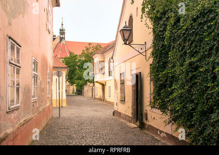 Koszeg street view. Small cosy street, old city in a historic medieval old town. Romantic cobbled side street. Green overgrown facade, peace and quiet. - Stock Photo